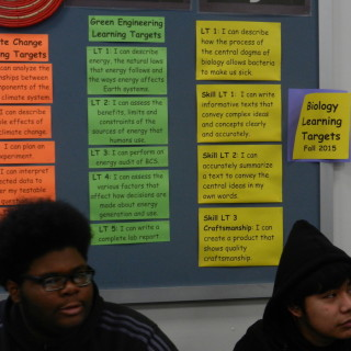 Two students sit in front of the learning target wall and listen to Beth Mowry in her climate change class at Brooklyn School for the Collaborative Studies, November 19, 2015.
